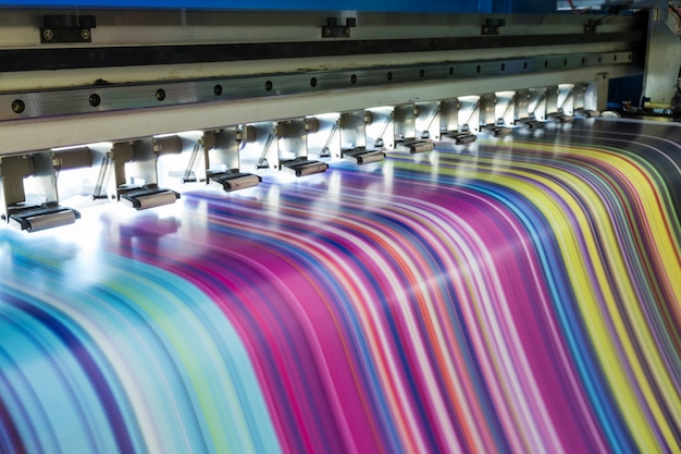 Grande imprimante à jet d'encre fonctionnant en plusieurs couleurs sur une bannière en vinyle