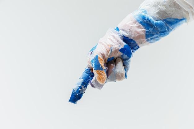Grande main en plastique faite d'ordures sur blanc