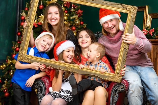 Grande maison de famille souriante de bonheur en chapeaux de santa helper
