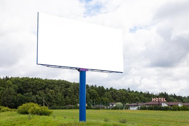 Grande maquette de panneau d'affichage vide le long de l'autoroute et de l'hôtel en arrière-plan