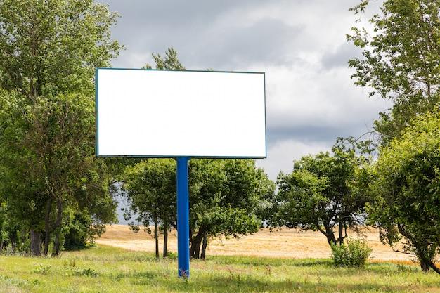 Grande maquette de panneau d'affichage vide le long de la route contre le pré avec des arbres