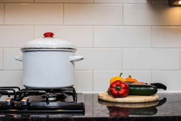 Une grande marmite sur une cuisinière avec des légumes coupés pour faire de la soupe