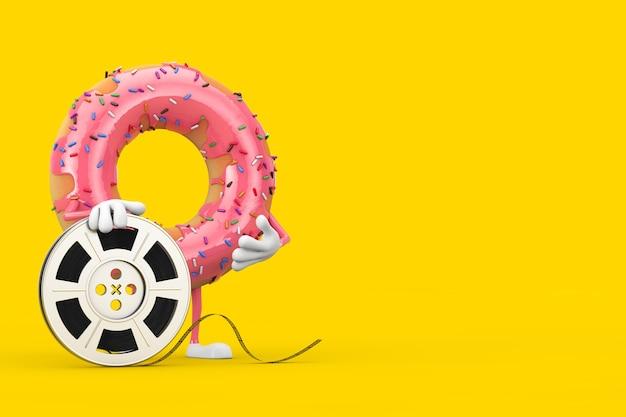 Grande mascotte de personnage de beignet glacé rose fraise avec bande de cinéma de bobine de film sur fond jaune. rendu 3d