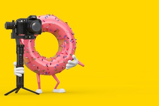 Grande mascotte de personnage de beignet glacé rose fraise avec dslr ou système de trépied de stabilisation de cardan de caméra vidéo sur fond jaune. rendu 3d