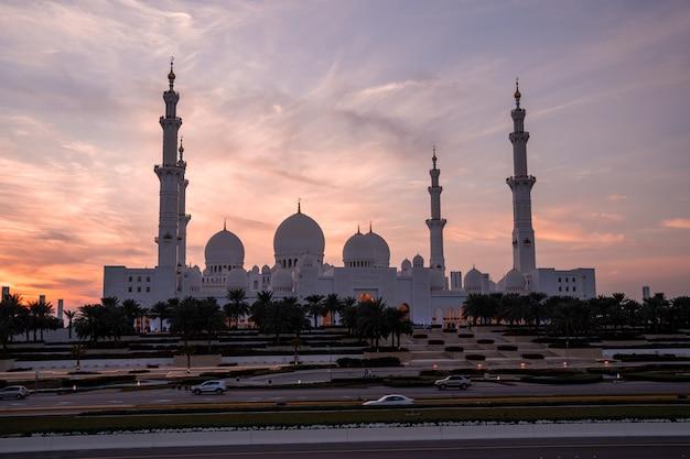 Grande mosquée d'abu dhabi le soir au coucher du soleil. panorama de l'extérieur de la mosquée sheikh zayed aux émirats arabes unis.