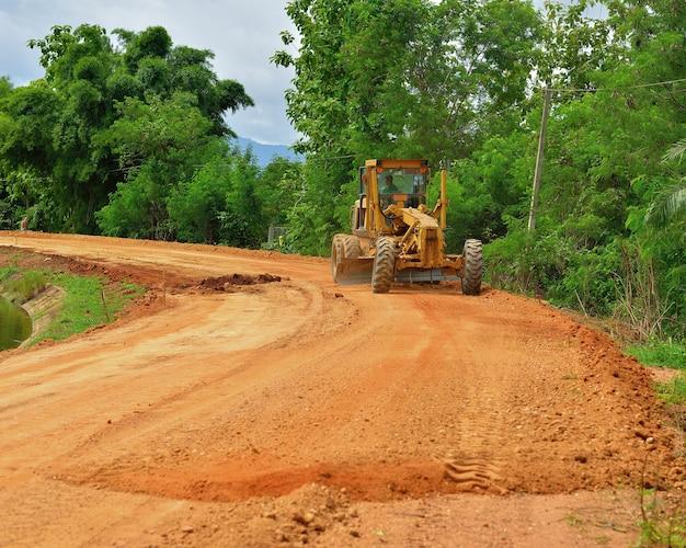 Grande niveleuse une route rurale étroite