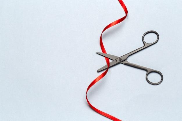 Grande ouverture illustrée avec des ciseaux et un ruban rouge sur un gris