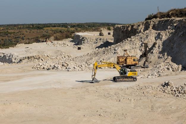 Une grande pelle à chenilles jaune extrait de la roche dans une carrière.