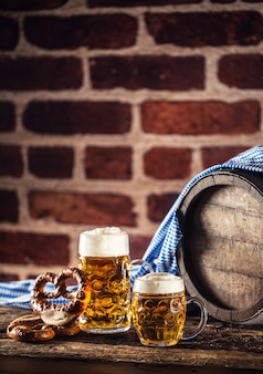 Grande et petite bière oktoberfest avec tonneau en bois de bretzel et nappe bleue.
