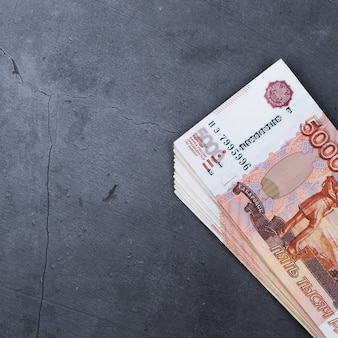 Grande pile de billets en argent russe de cinq mille roubles gisant sur un fond de ciment gris.