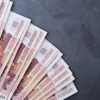 Grande pile de billets en argent russe de cinq mille roubles ventilateur couché sur un fond de ciment gris.