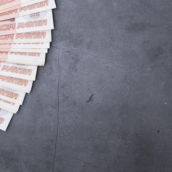 Grande pile de billets de banque russes de cinq mille roubles, reposant sur un ciment gris.