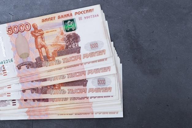 Grande pile de billets de banque russes de cinq mille roubles se trouvant sur un ciment gris