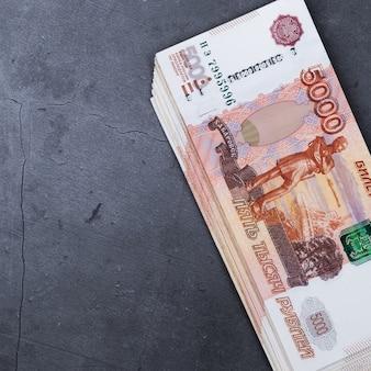 Grande pile de billets de banque russes de cinq mille roubles se trouvant sur du ciment gris
