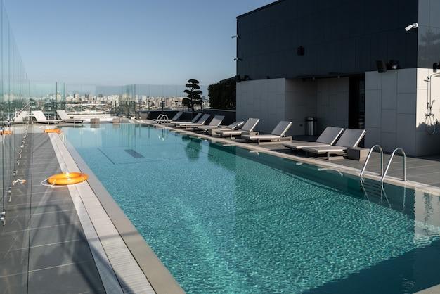 Grande piscine moderne avec transats et bouées de sauvetage. le concept de récréation