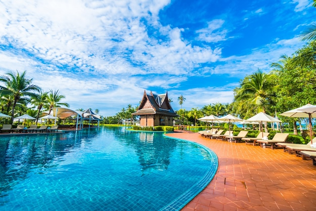 Grande piscine avec des parasols et des hamacs