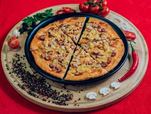 Grande pizza chaude sur la plaque noire.