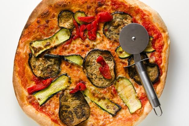 Grande pizza italienne aux légumes grillés isolé sur table blanche et couteau
