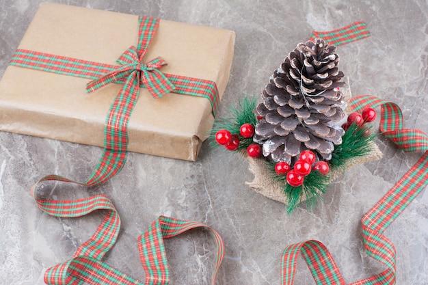 Grande pomme de pin de noël festive avec présent et archet sur fond de marbre.