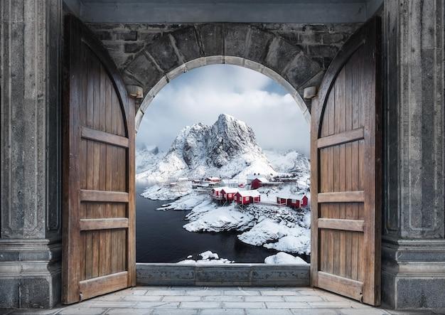 Grande porte en bois ouverte avec village de pêcheurs et montagnes rocheuses sur le littoral en hiver à hamnoy, îles lofoten, norvège