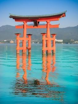 La grande porte du sanctuaire japonais orange sur l'eau dans la mer