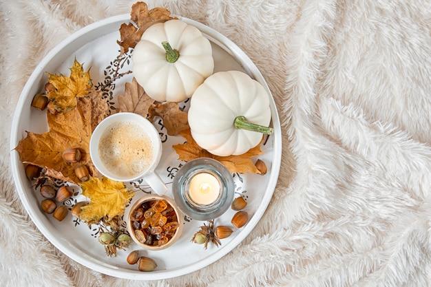 Grande portion en bois avec une tasse de café avec du sucre brun, des bougies allumées. décoration saisonnière de feuillage et de citrouilles.