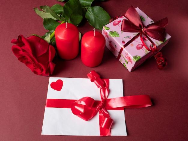 Une grande rose rouge qui est à côté de deux grandes bougies rouges et un cadeau rose