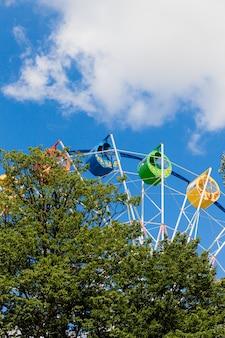 Grande roue aux couleurs vives dans le parc contre un ciel bleu avec des nuages.