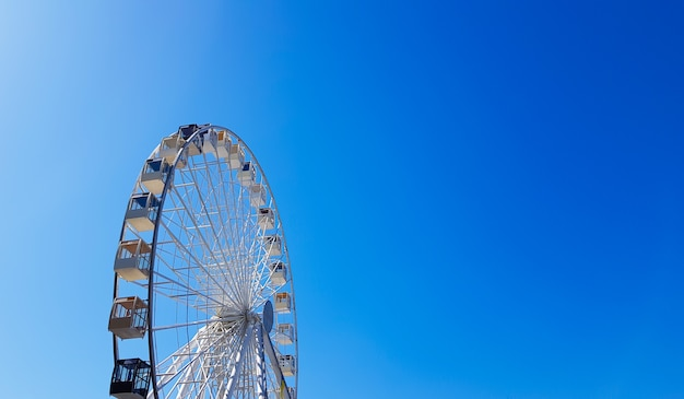 Grande roue blanche contre le ciel bleu. une partie de l'attraction sur fond bleu avec espace de copie. cabines, plateformes d'observation.