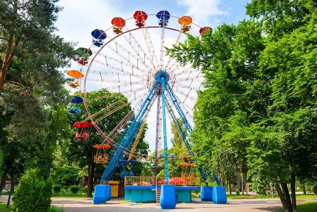 Grande roue dans le parc verdoyant sur ciel bleu avec des nuages