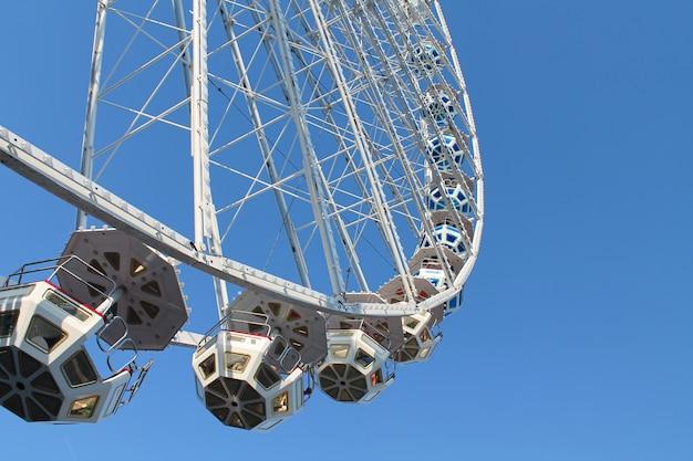 Grande roue de fête foraine sur fond de ciel bleu.