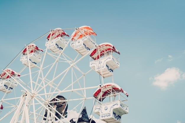 Grande roue sur fond de ciel nuageux avec des tons vintage.
