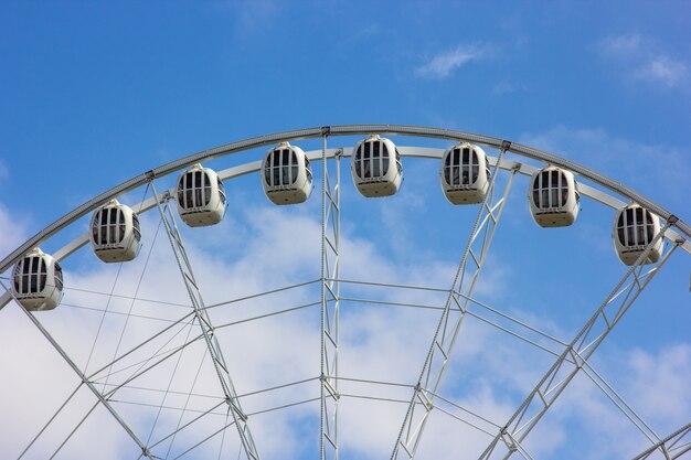Grande roue moderne contre un ciel bleu avec des nuages