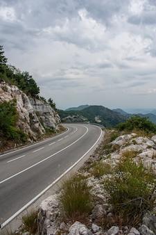 Grande route vide avec virage à gauche dans les montagnes et beau ciel