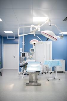 Grande salle d'opération à l'intérieur de cliniques contemporaines comprenant une table d'opération entourée de lampes, un équipement de diagnostic et un ensemble de tiroirs
