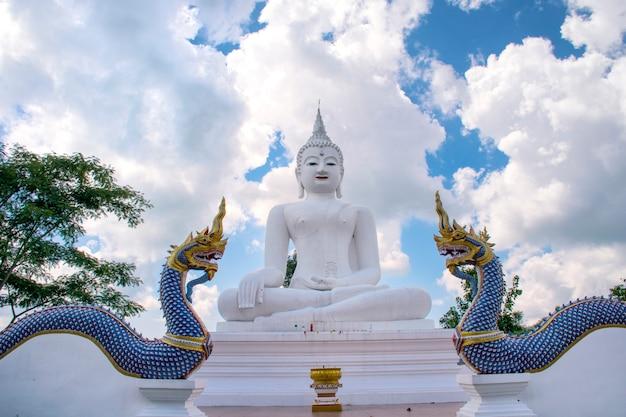 Grande statue blanche de bouddha et roi des nagas avec un ciel bleu, wat chom tham, à chiang mai, thaïlande