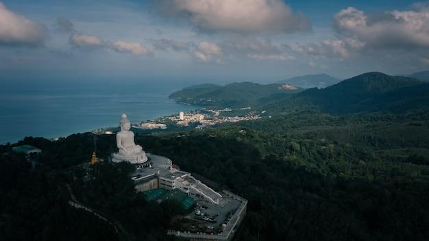 Grande statue de bouddha blanc au sommet d'un point de vue sur la montagne et d'une destination historique