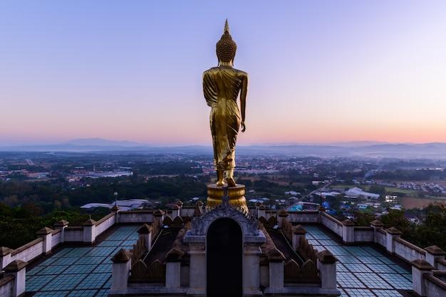 Grande statue de bouddha doré debout dans le wat phra that kao noi le matin dans la province de nan en thaïlande,