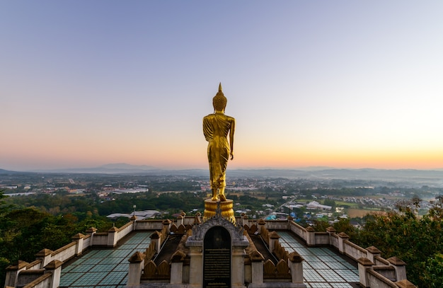 Grande statue de bouddha en or debout dans wat phra that kao noi le matin à la province de nan thaïlande