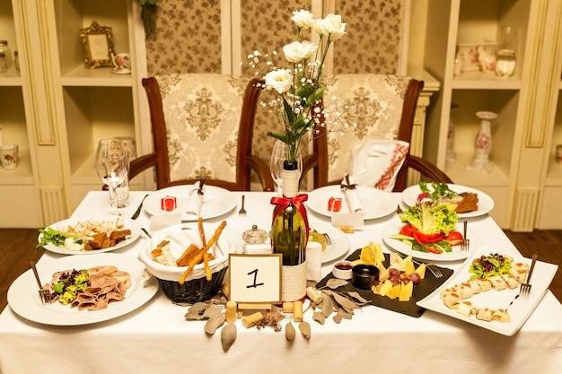 Une grande table de restaurant, créée pour un grand nombre de personnes, est rangée, avec une nappe blanche sur laquelle se dresse une bouteille de fleurs. table de restaurant blanche avec des fleurs dans une bouteille