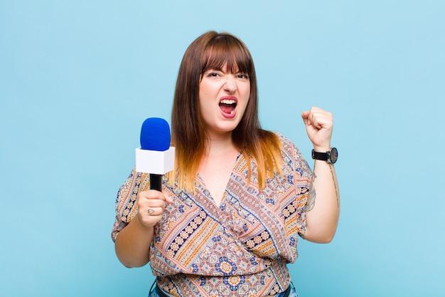 Grande taille femme criant agressivement avec une expression de colère ou avec les poings fermés célébrant le succès