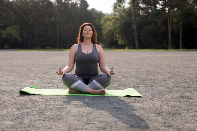 Grande taille, fille, méditer, yoga, dehors