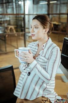 Grande tasse blanche. femme d'affaires rayonnante enceinte tenant une grande tasse blanche en buvant du thé
