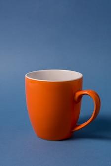 Grande tasse orange isolée sur fond bleu.