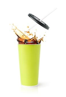 Grande tasse verte avec cola splash isolé sur une surface blanche