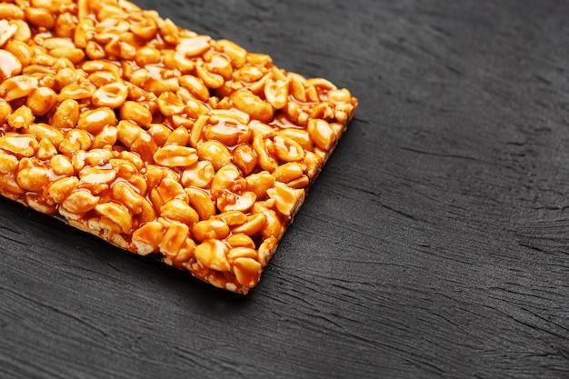 Une grande tuile dorée de cacahuètes, une barre dans une mélasse douce. kozinaki bonbons utiles et savoureux de l'est
