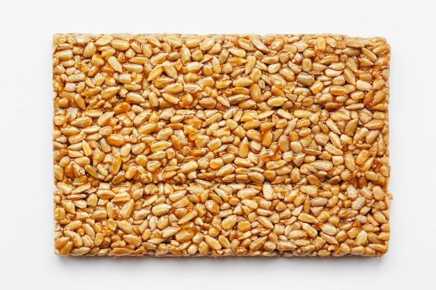 Une grande tuile dorée de graines de tournesol, une barre dans une mélasse douce. kozinaki bonbons utiles et savoureux de l'est