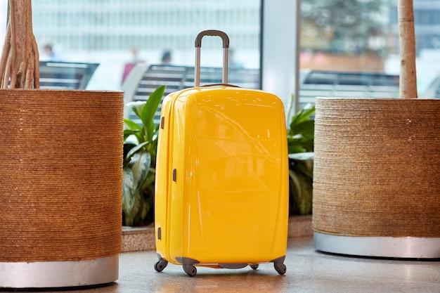Grande valise jaune à roulettes à l'aéroport.