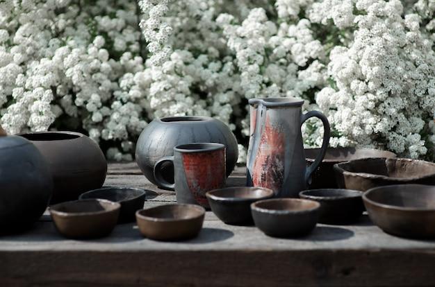 Une grande variété de poterie noire d'argile sur fond de fleurs blanches