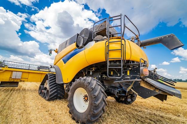 Grande vue sur moissonneuse-batteuse jaune. technique spéciale dans le domaine. machines modernes en blé d'or.